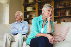 Upset senior couple ignoring each other in living room. At home Stock Images