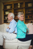Upset senior couple ignoring each other in living room Stock Photos