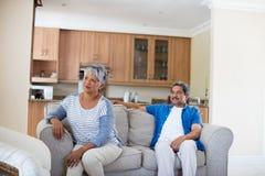 Upset senior couple ignoring each other in living room Stock Photo