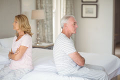 Upset senior couple sitting back to back on bed. In bedroom Stock Image
