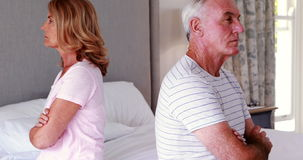 Upset senior couple sitting back to back on bed. In bedroom stock footage