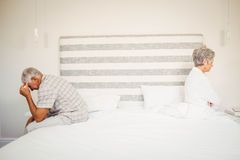 Upset senior couple sitting on the opposite ends of the bed. After a fight royalty free stock photos