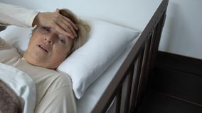 Upset senior female lying in hospital bed, touching forehead with trembling hand. Stock footage stock footage