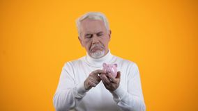 Upset senior male putting coin in piggy bank, poor budget, low pension concept