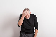 Upset senior man with headache, holding his head, studio shot. Royalty Free Stock Image