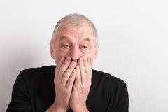 Upset senior man with headache, holding his mouth, studio shot. Stock Image