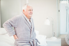 Upset senior man sitting with back pain on bed Royalty Free Stock Images