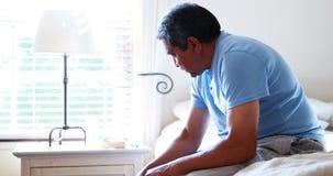 Senior man sitting in bedroom 4k stock video