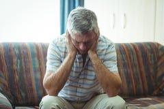 Upset senior man sitting in living room Stock Image