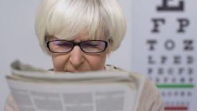 Upset senior woman in eyeglasses reading newspaper, vision problems, illness