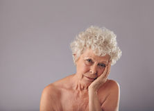 Upset senior woman on grey background Royalty Free Stock Photography