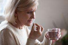Upset senior woman holding pill and glass water taking medicine stock photos