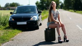 Upset girl sitting on rusty canister on road stock footage