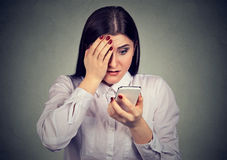 Upset shocked serious woman looking at her mobile phone. Royalty Free Stock Photo