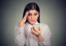 Upset shocked serious woman looking at her mobile phone. Upset shocked serious young woman looking at her mobile phone royalty free stock photos