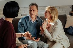 Upset short-haired man in blue sweater explaining his issues. Expressing feelings. Upset short-haired men in blue sweater explaining his issues to attentive royalty free stock images