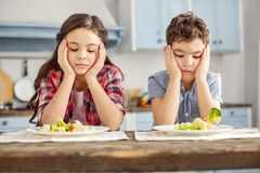 Upset siblings looking sadly at the vegetables Stock Photography