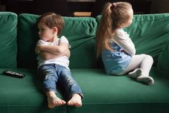 Upset siblings sitting on sofa ignoring each other after fight. Upset siblings boy and girl sulking sitting with arms crossed on sofa not talking, kids brother royalty free stock images