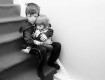 Upset Children. Upset siblings sitting on the stairs Stock Photo