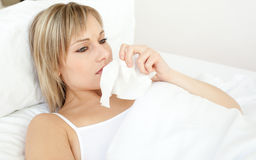 Upset sick woman blowing lying on her bed. At home Royalty Free Stock Image