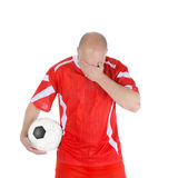 Upset soccer player in the red form. Stock Photos