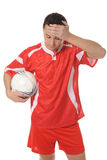 Upset soccer player in the red form. Royalty Free Stock Images