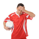 Upset soccer player in the red form. Royalty Free Stock Image