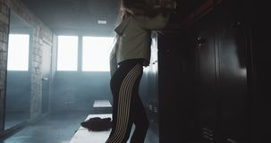 Upset sporty European woman feeling angry and furious alone in dark gym locker room, tired after bad day slow motion. Failure and dealing with motivation stock video footage