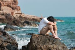 Upset stressed Asian man bend down head at sea shore. Upset stressed Asian man bend down head at sea shore Stock Images