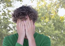 Upset stressed man hiding in hands under trees Royalty Free Stock Images