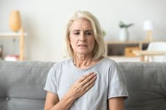 Upset stressed mature older woman feeling heartache touching che stock images