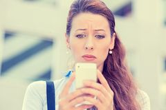 Upset stressed woman holding cellphone disgusted with message she received. Corporate building background. Sad looking human face expression emotion feeling stock images