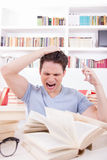 Upset student with hand on his head surrounded by books Stock Images