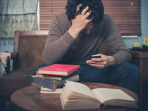 Upset student using his smartphone Royalty Free Stock Photography
