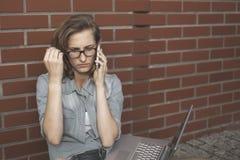Upset student wornikg with laptop, thinking of something. Sitti Royalty Free Stock Image