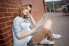Upset student wornikg with laptop, thionking of something. Sitting next to the brick wall. Royalty Free Stock Image