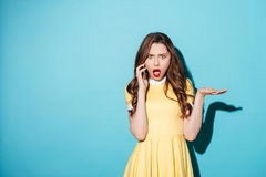 Upset surprised girl in dress talking on mobile phone Stock Photos