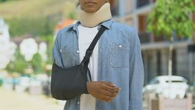 Upset teen boy wearing foam cervical collar and broken hand bandage, accident. Stock footage stock video