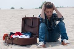 Upset teenage boy sitting on beach near suitcase Royalty Free Stock Image