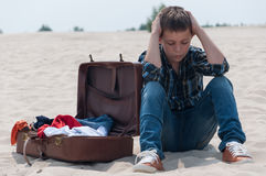 Upset teenage boy sitting on beach near suitcase. Upset teenage boy sitting on beach near open suitcase Royalty Free Stock Image