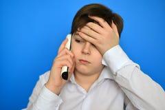 Upset teenage boy talking by radiotelephony Stock Photography