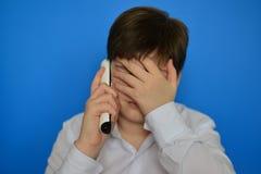 Upset teenage boy talking by radiotelephony Royalty Free Stock Photo