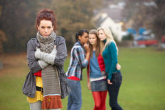 Upset Teenage Girl With Friends Gossiping. In Background Royalty Free Stock Photos