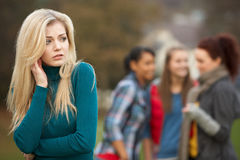 Upset Teenage Girl With Friends Gossiping. In Background Royalty Free Stock Photography