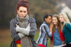 Upset Teenage Girl With Friends Gossiping. In Background Stock Photo