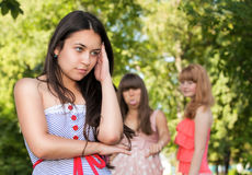 Upset teenage girl with friends gossiping Royalty Free Stock Image