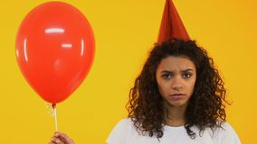 Upset teenage girl holding balloon, feeling lonely on birthday party, no friends stock video footage