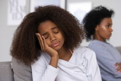 Upset teenage girl sad after fight with mom. Sad African American teenage daughter sit on couch feel upset after fight with mom, mother and child avoid talking royalty free stock images