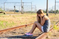 Upset teenager girl sitting on rail track in countryside Royalty Free Stock Photos