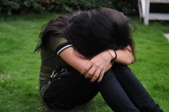 Upset teenager girl sulking in the garden. Stock Photography